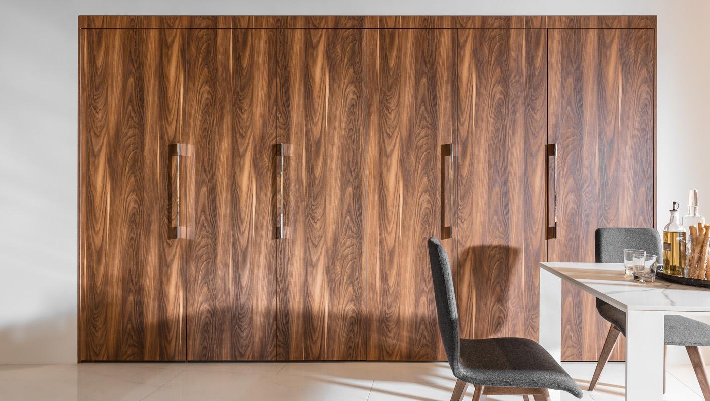 Drzwi przesuwne w kuchni. Kuchnia ukryta za drzwiami w kolorze drewna.