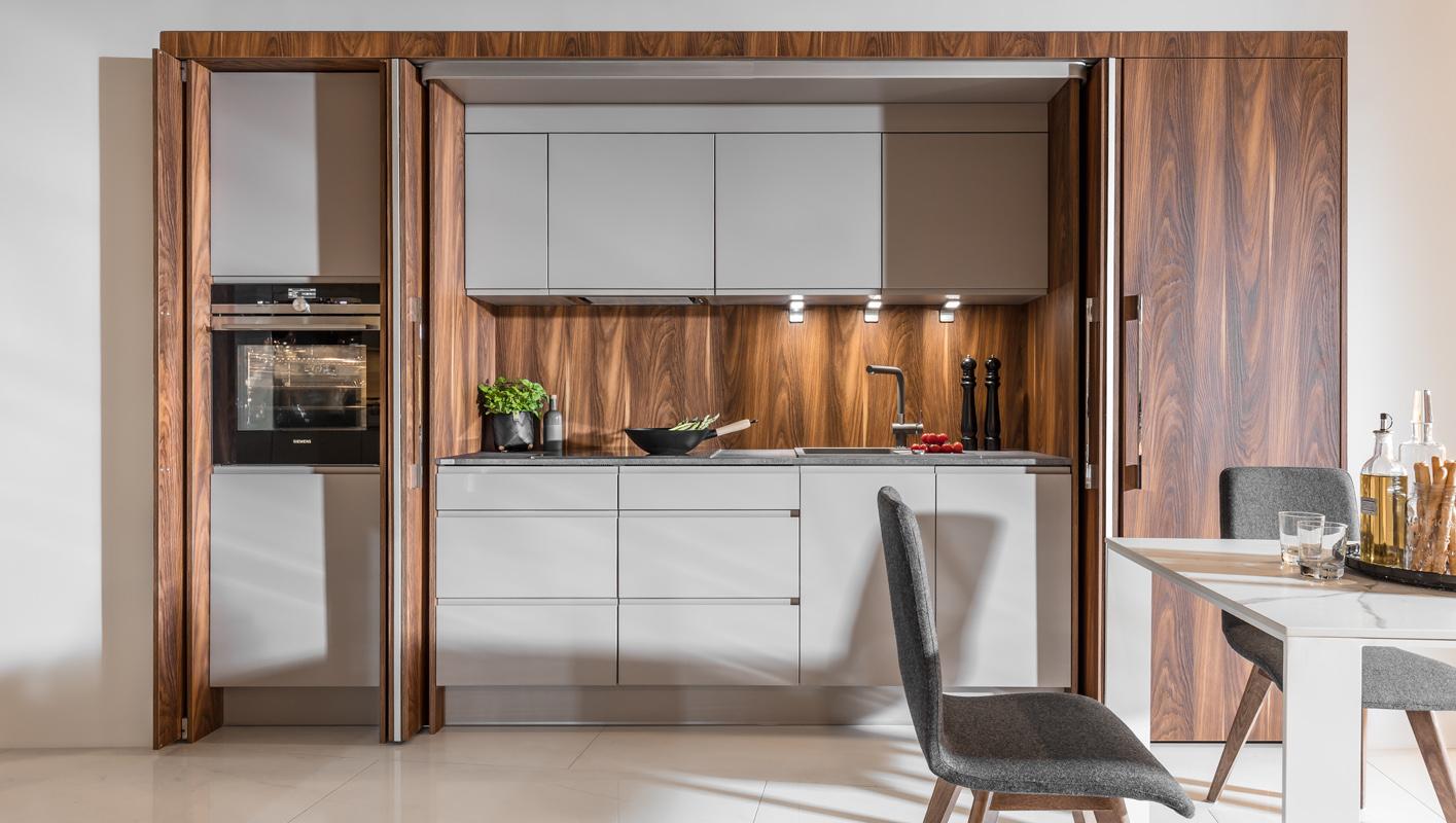 Drzwi przesuwne w kuchni. Kuchnia ukryta za drzwiami w kolorze drewna. Szare meble kuchenne bez uchwytów.