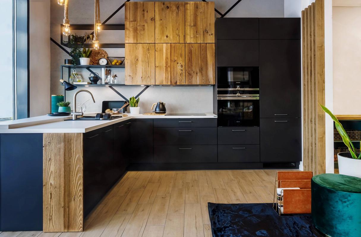 Kuchnia w kształcie L. Czarne meble kuchenne z drewnem. Drewno naturalne w kuchni. Lodówka i okap do zabudowy,