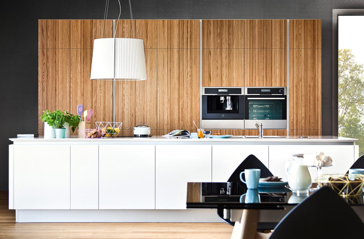 Meble kuchenne z dębu naturalnego połączonego z białymi frontami. Ekspres do kawy w zabdowie wysokiej, Biała wyspa kuchenna.