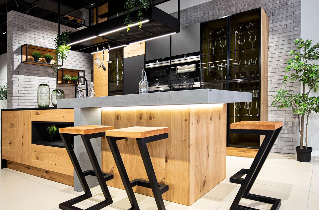 Meble kuchenne w kolorze dębu sękatego. Kuchnia z wyspą i hokerami do siedzenia. Metalowe szafki otwarte. Przeszklone witryny w kuchni.
