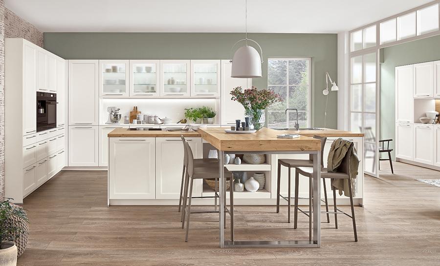 Biała kuchnia klasyczna z drewnianym blatem. Kuchnia z wyspą i ladą do siedzenia.