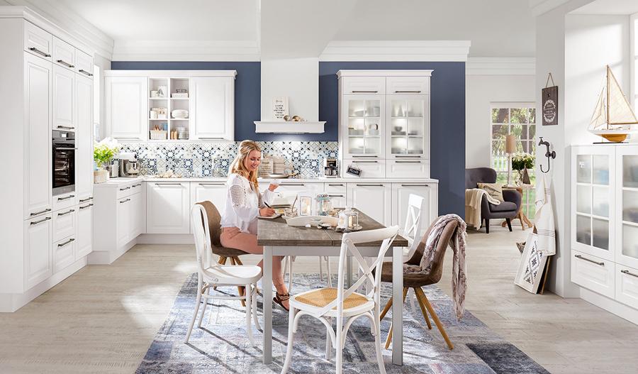 Biała klasyczna kuchnia. Granatowe elementy w kuchni. Witryny przeszklone.