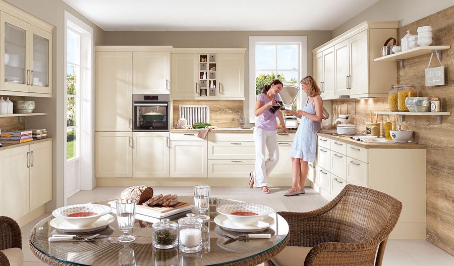 Klasyczna kuchnia w kształcie L. Meble kuchenne w kolorze magnolia. Blat kuchenny w kolorze drewna.