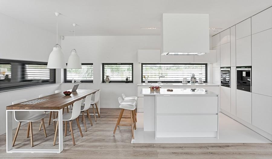 Biała kuchnia z wyspą. Kuchnia bez uchwytów. Stół w kuchni.