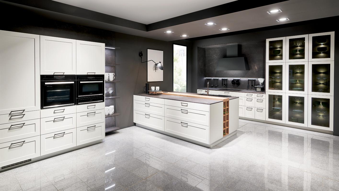 Biała kuchnia klasyczna z uchwytami meblowymi. Witryny przeszklone w kuchni.