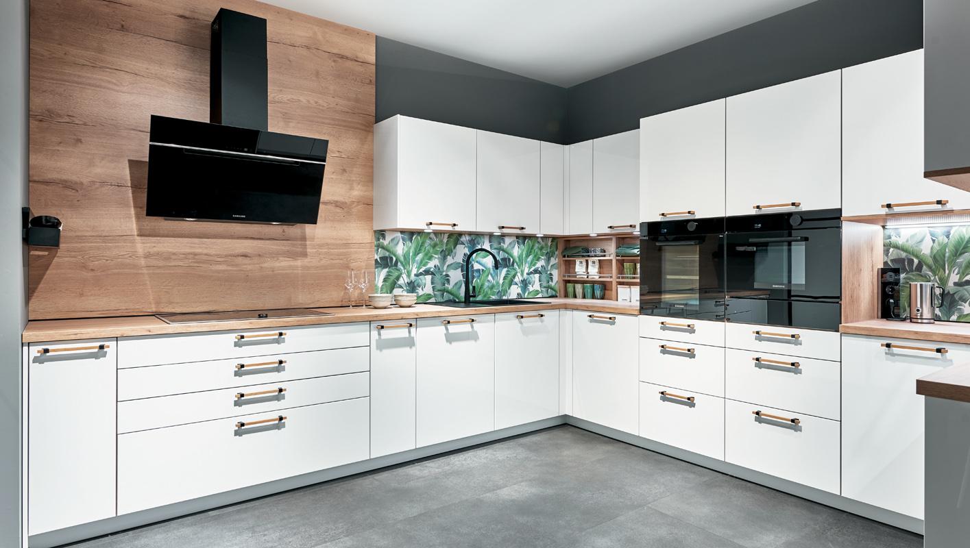 Meble kuchenne z uchwytem z drewna. Biała kuchnia z elementami drewnianymi. Meble kuchenne w kształcie L.