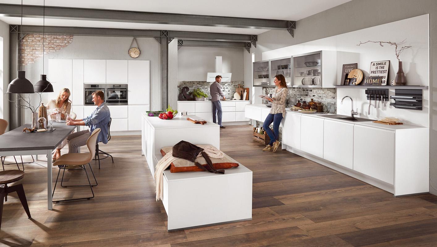 Białe meble kuchenne bez uchwytów. Duża, nowoczesna kuchnia ze stołem i wyspą/