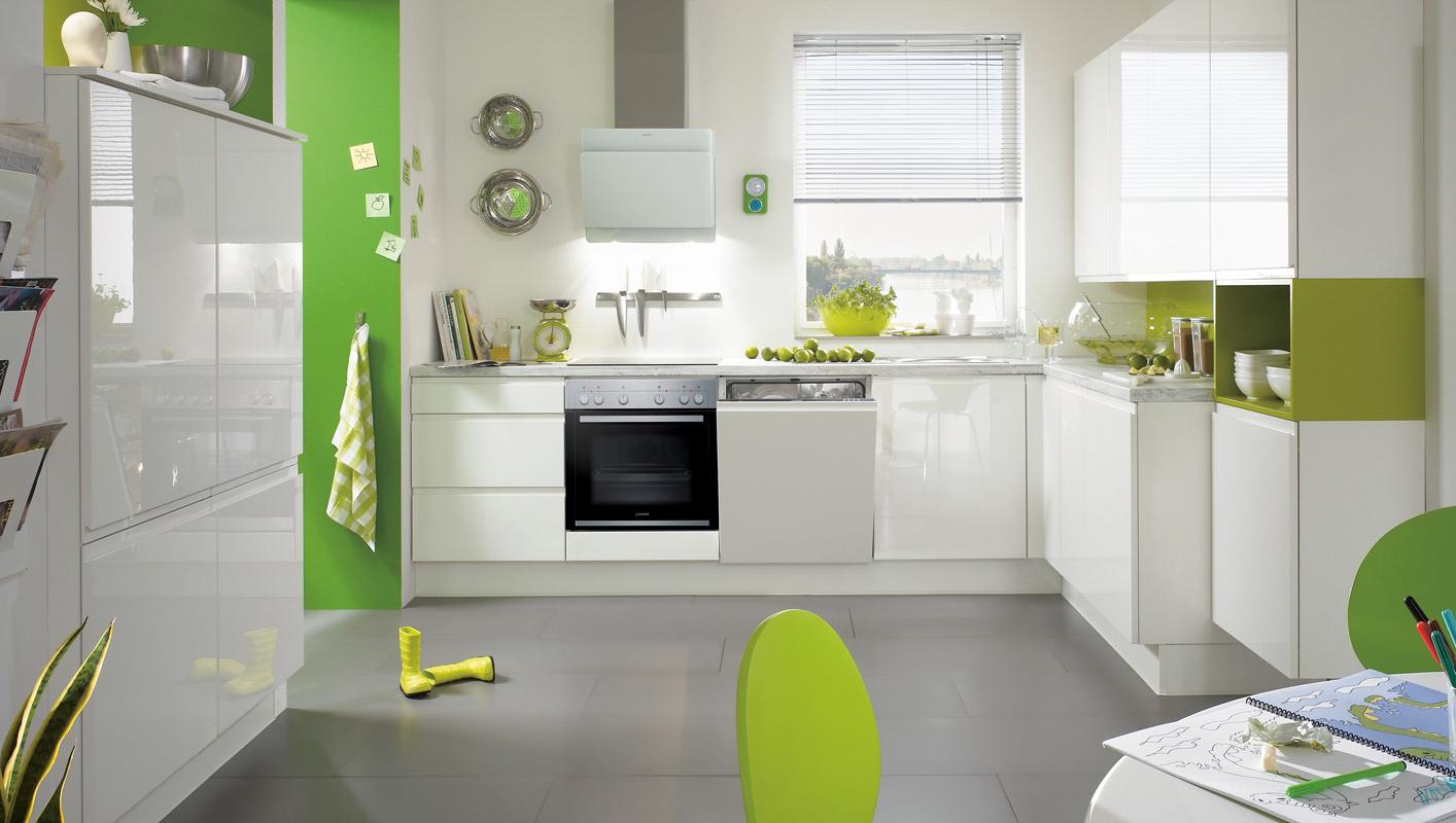 Biała kuchnia bezuchwytowa. Okap wolnowiszący. Zielone akcenty w kuchni.