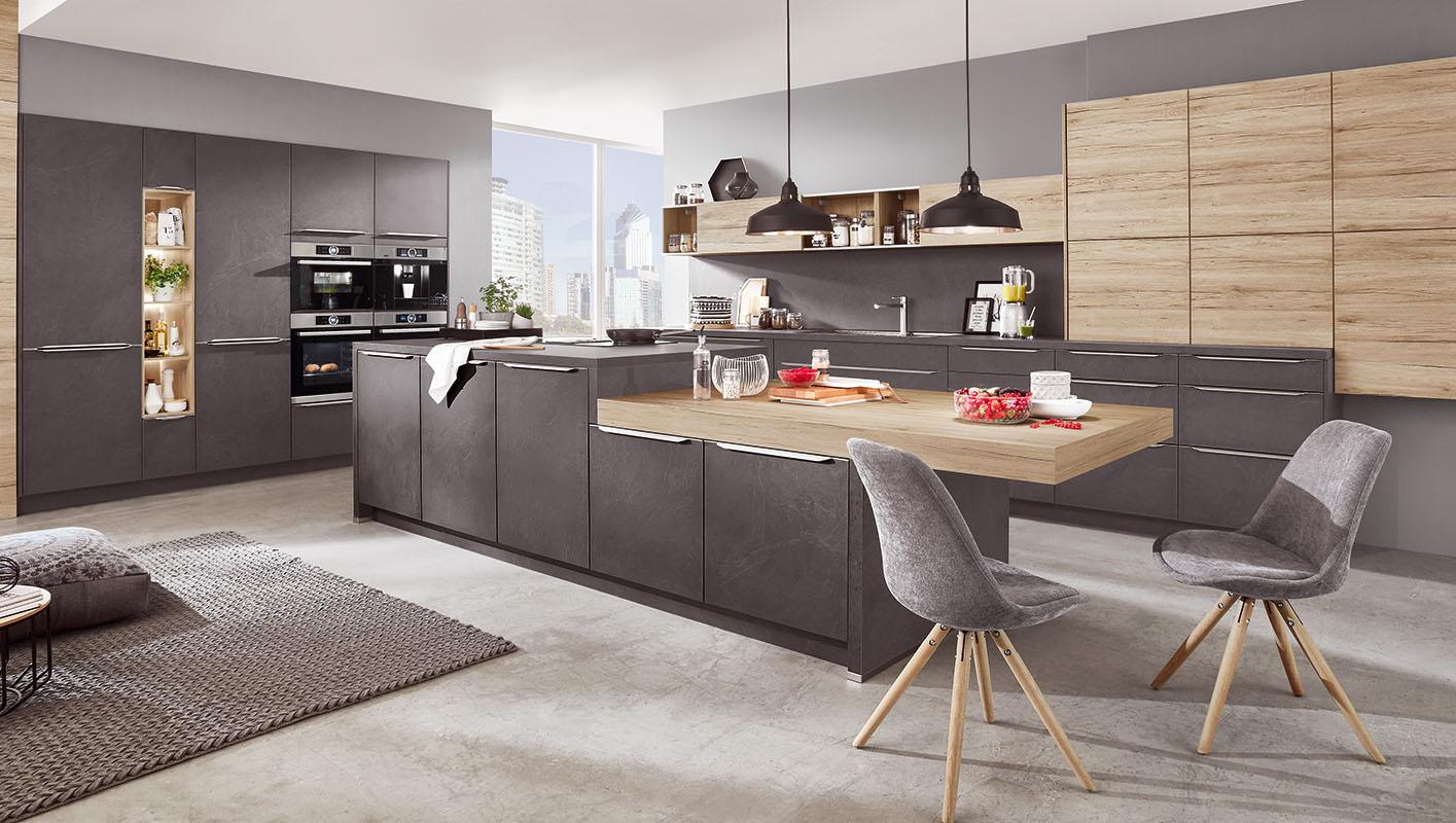 Kuchnia w kolorze ciemnego betonu ocieplona elementami w kolorze drewna. Uchwyt krawędziowy. Obniżenie blatu kuchennego do wysokości krzeseł.