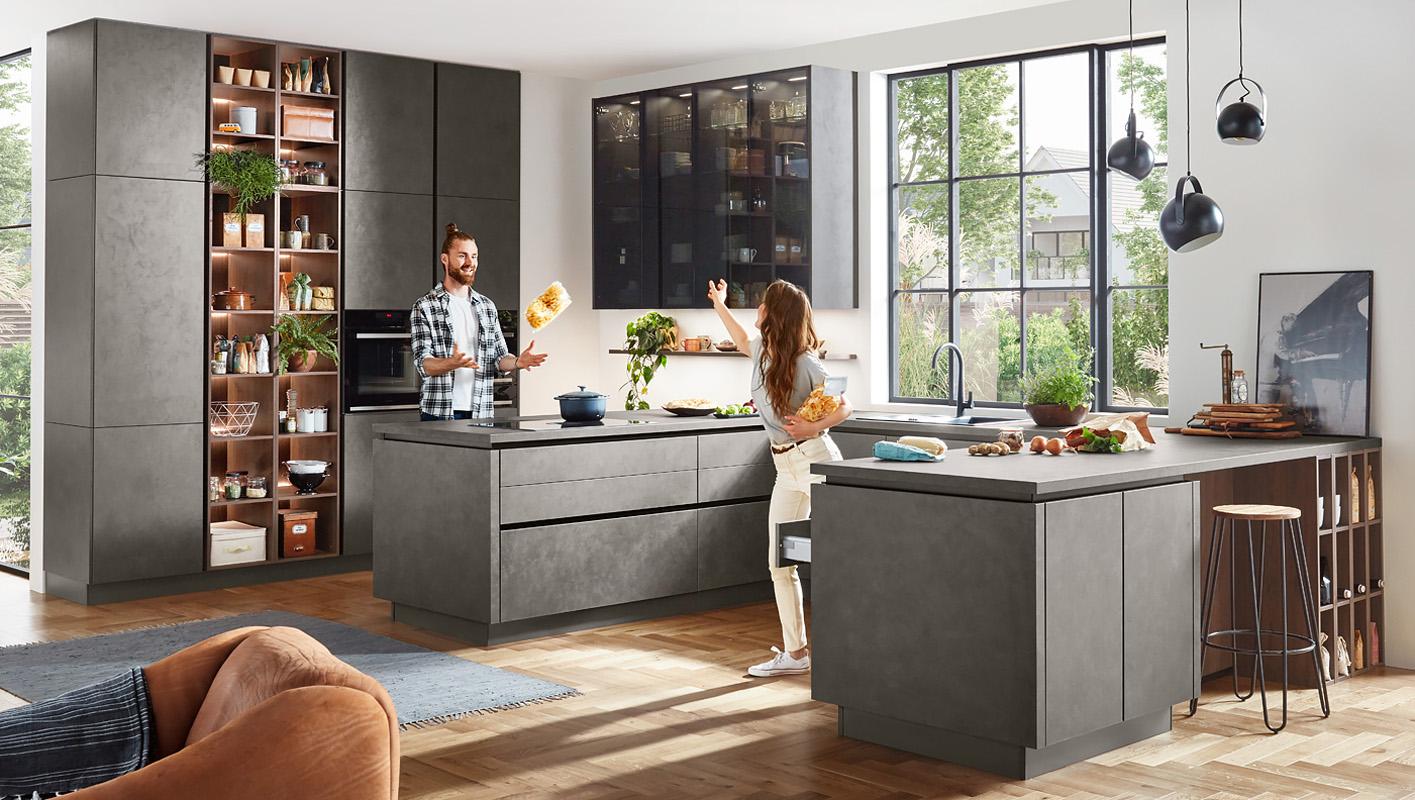 Nowoczesna kuchnia do sufitu w kolorze ciemnego betonu. Kuchnia bez uchwytów z listwami korytkowymi. Regały otwarte i witryny w kuchni.
