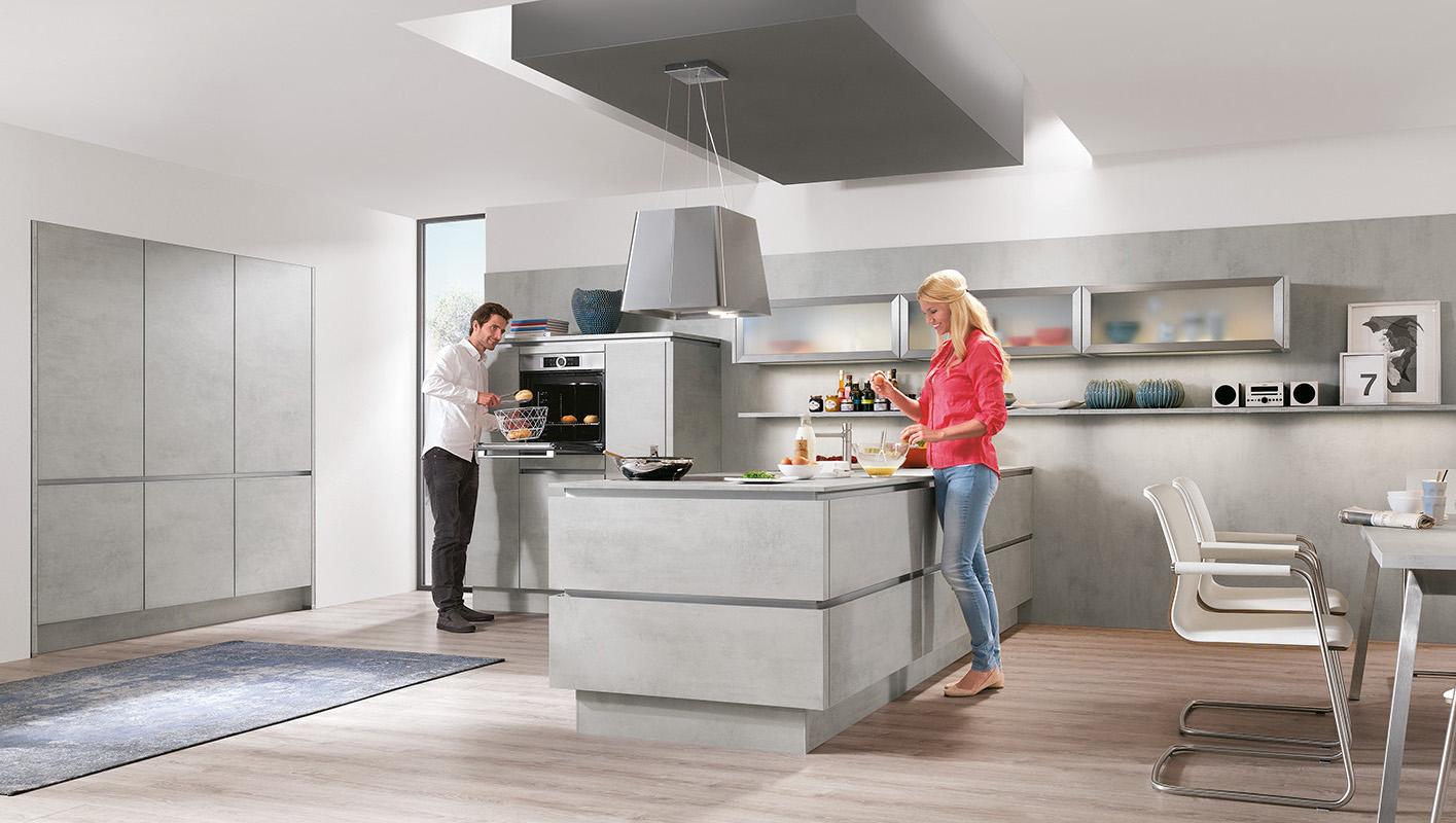 Kuchnia w kolorze szarego betonu. Szafki kuchenne bez uchwytów. Okap i zlew na półwyspie.